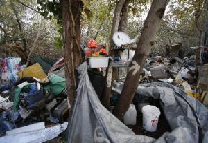 Crews tear down an elaborate shower used by the homeless inside the Jungle, as the notorious camp is closed on Dec. 4, 2014, in San Jose, Calif. Hundreds of homeless people were ordered out of their camps in the thickly-vegetated area. (Karl Mondon/Bay Area News Group)